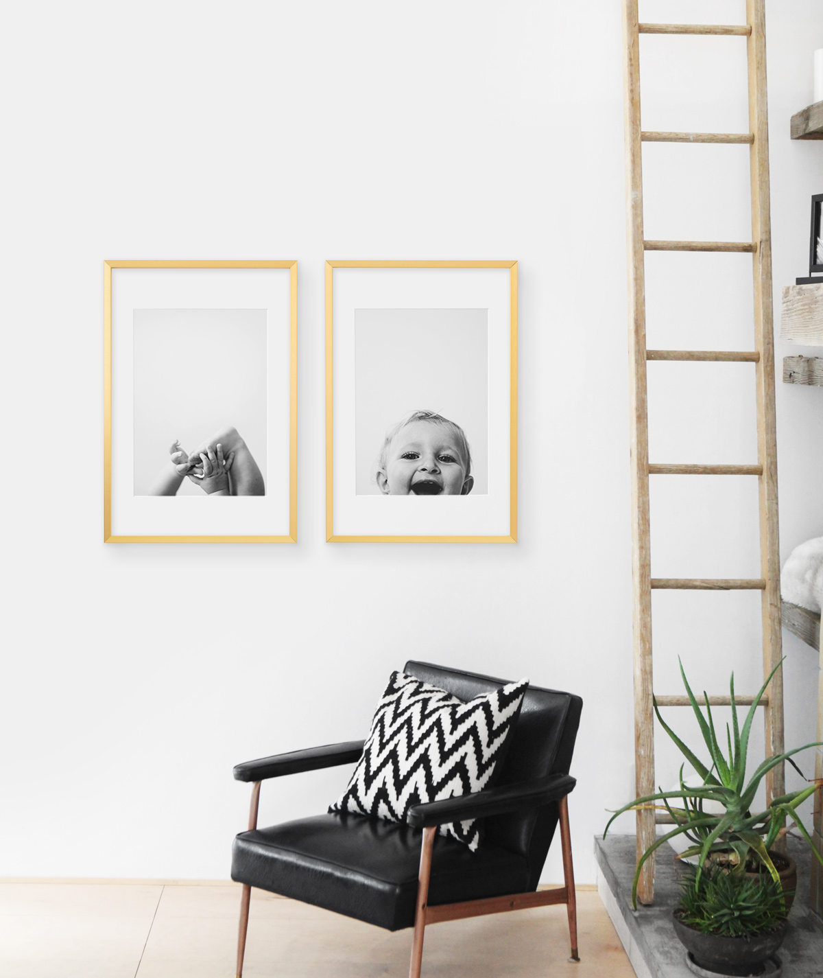 Baby pictures in brass frames hung up above modern leather chair