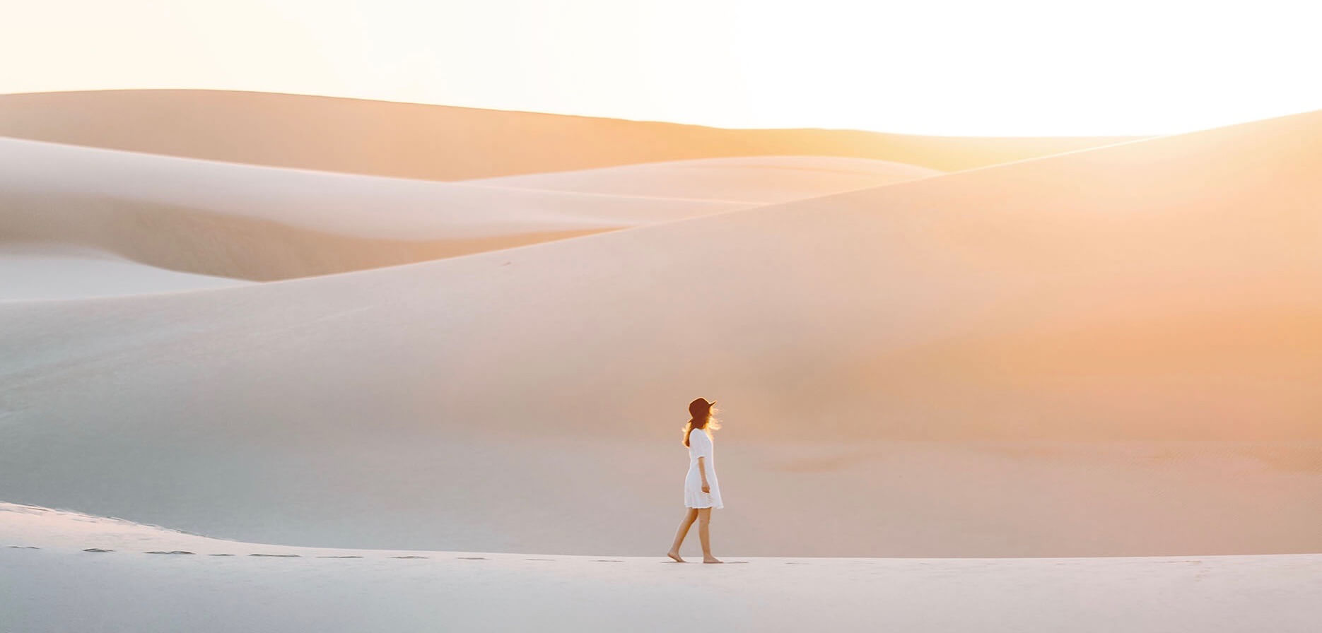 Emilie Ristevski photo of woman walking across sand dunes