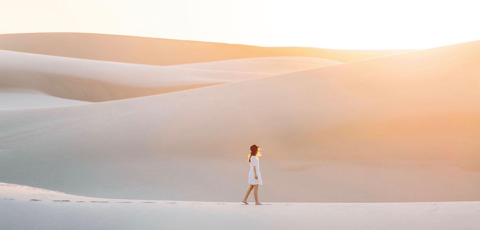 Emilie Ristevski photo of woman walking across sand dunes