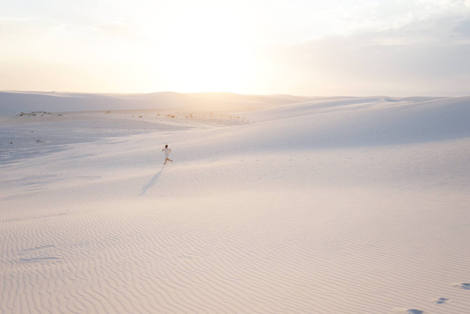Photo of woman running across sand in desert setting captured using tips on how to take better iPhone photos