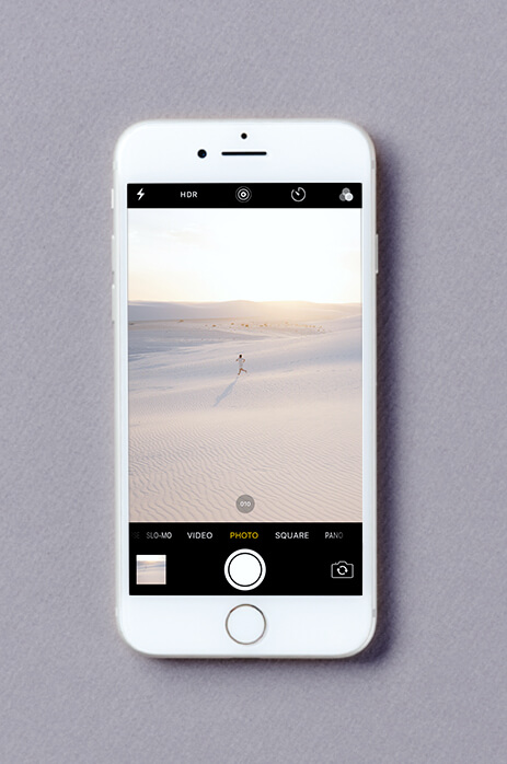iPhone screen in burst mode taking photos of woman running across the sand