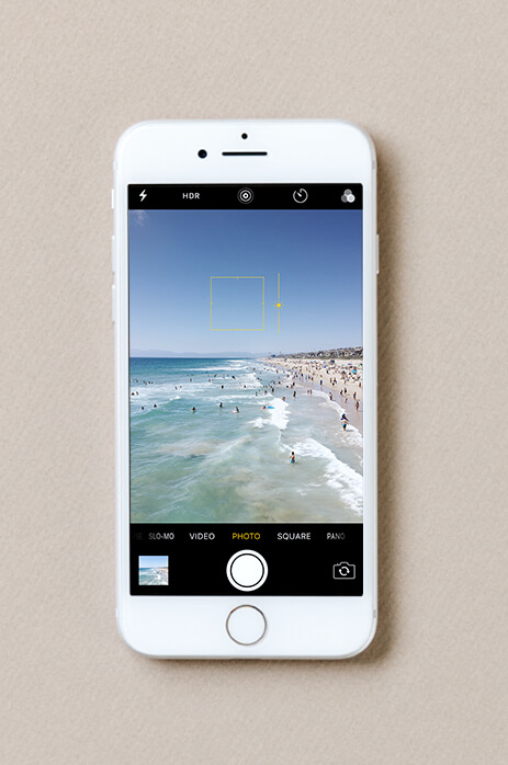 Photo of exposure being adjusted on iPhone taking photo of busy beach