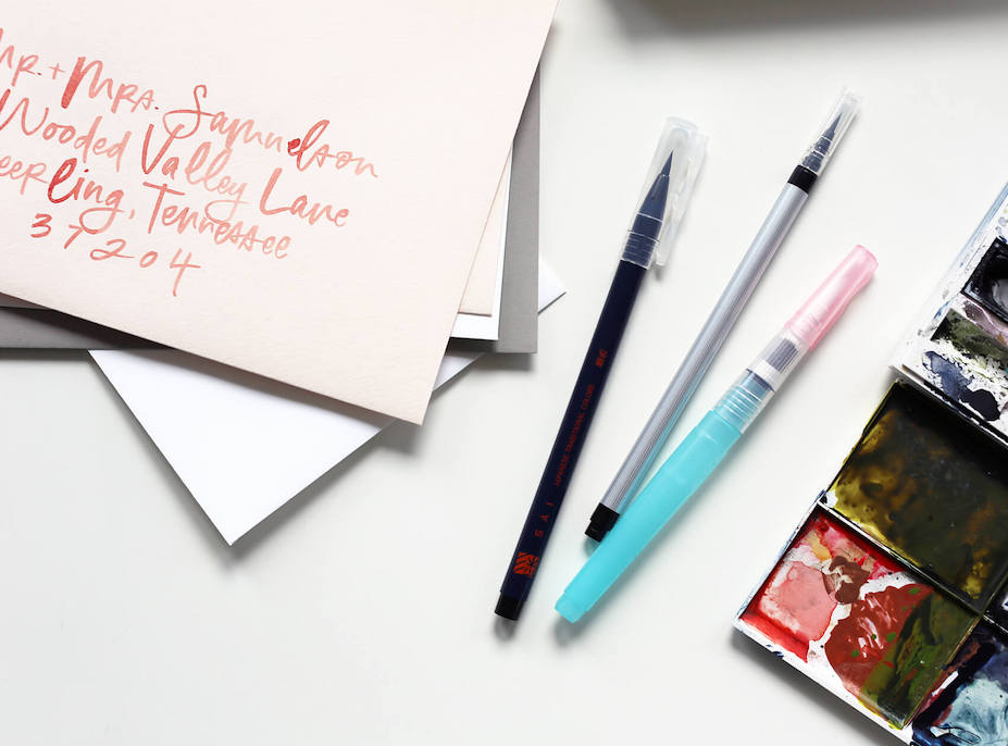 Pens next to envelopes addressed in calligraphy