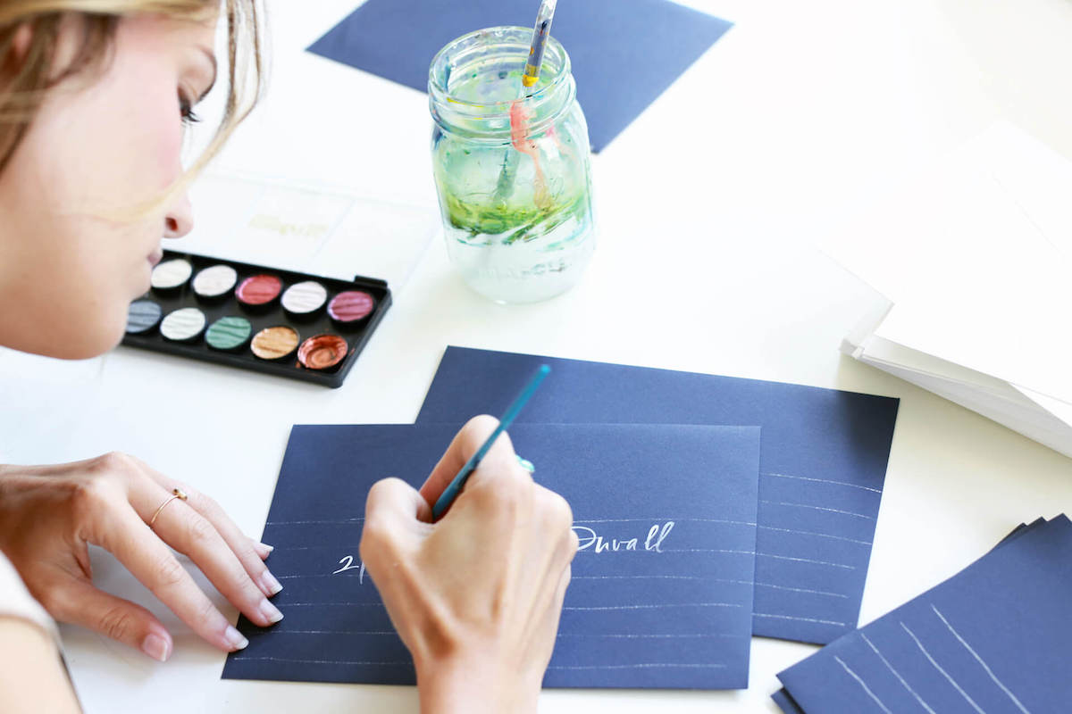 Chelsea Petaja addressing envelopes in calligraphy
