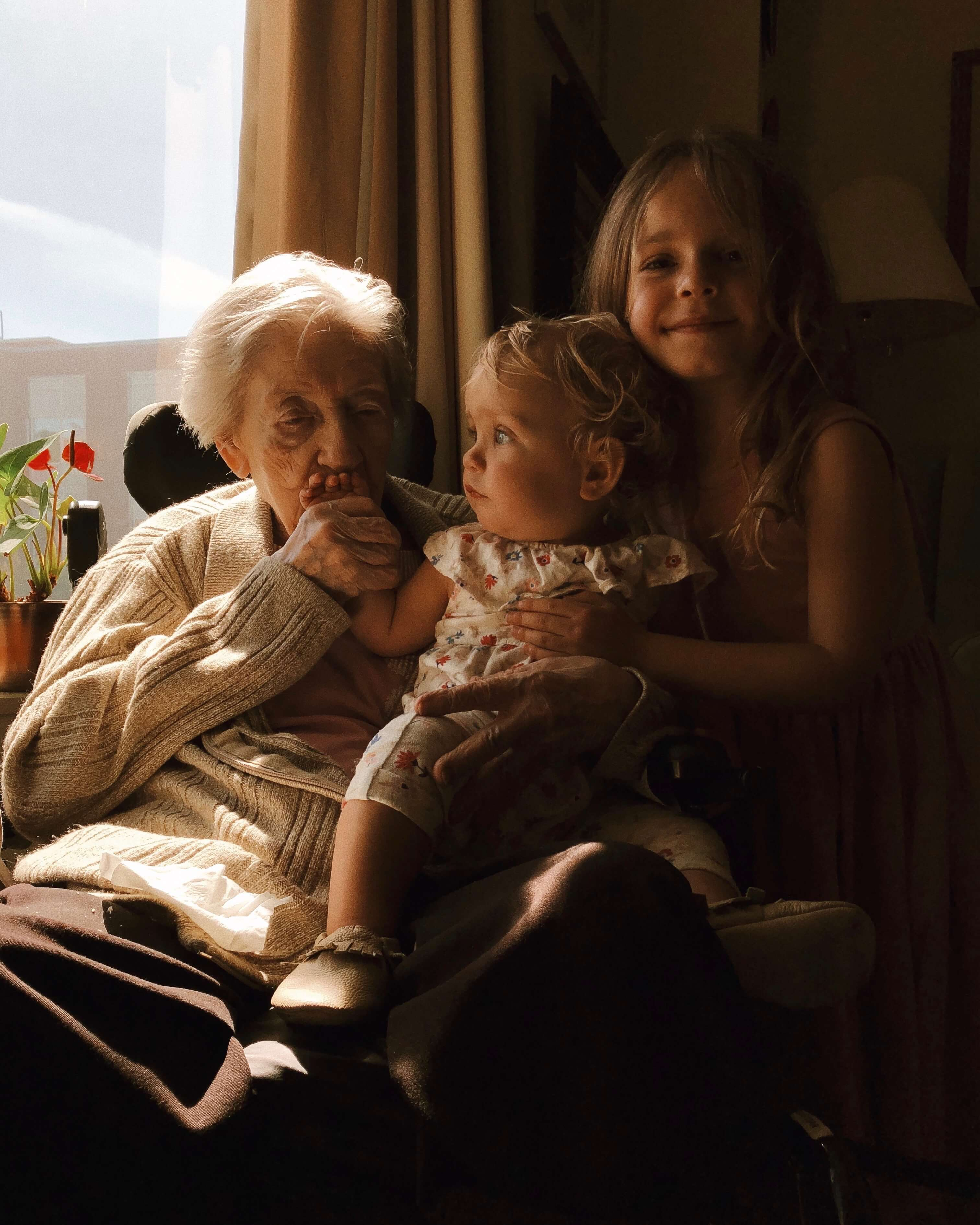 Grandmother with granddaughters by the window