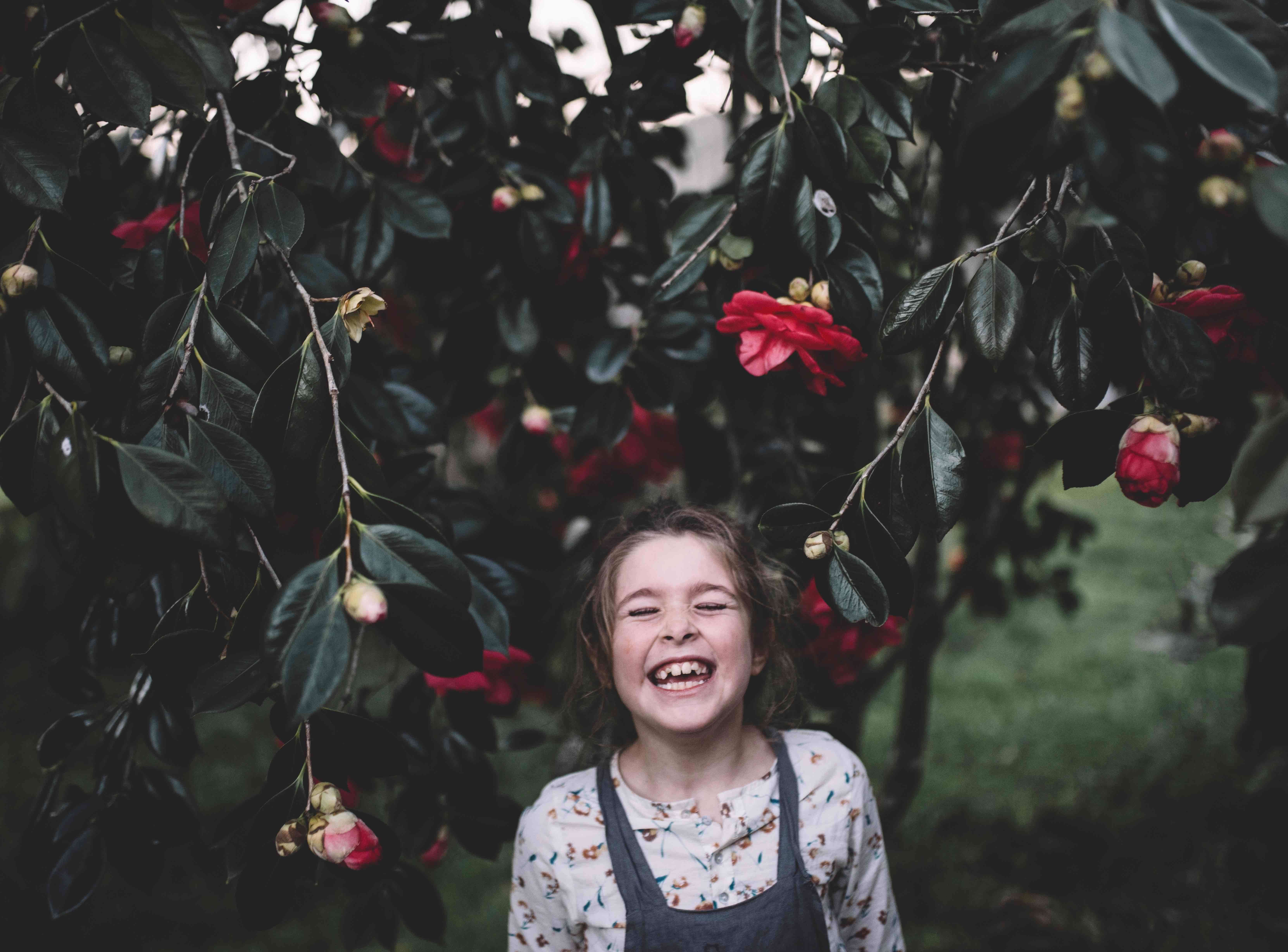 Young girl smiling with eyes closed under a flowering tree