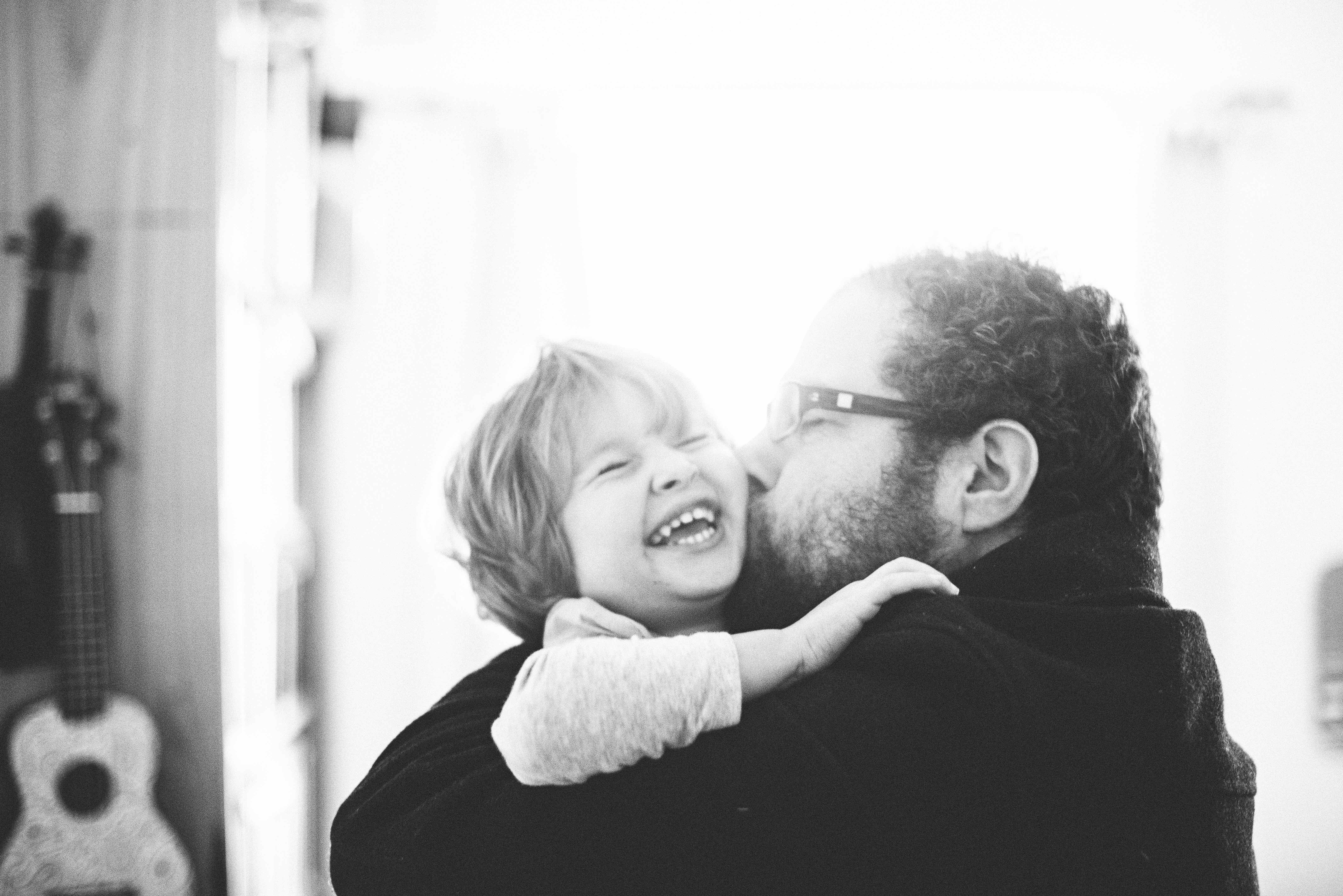 Black and white photo of father kissing little girl on cheek while she laughs