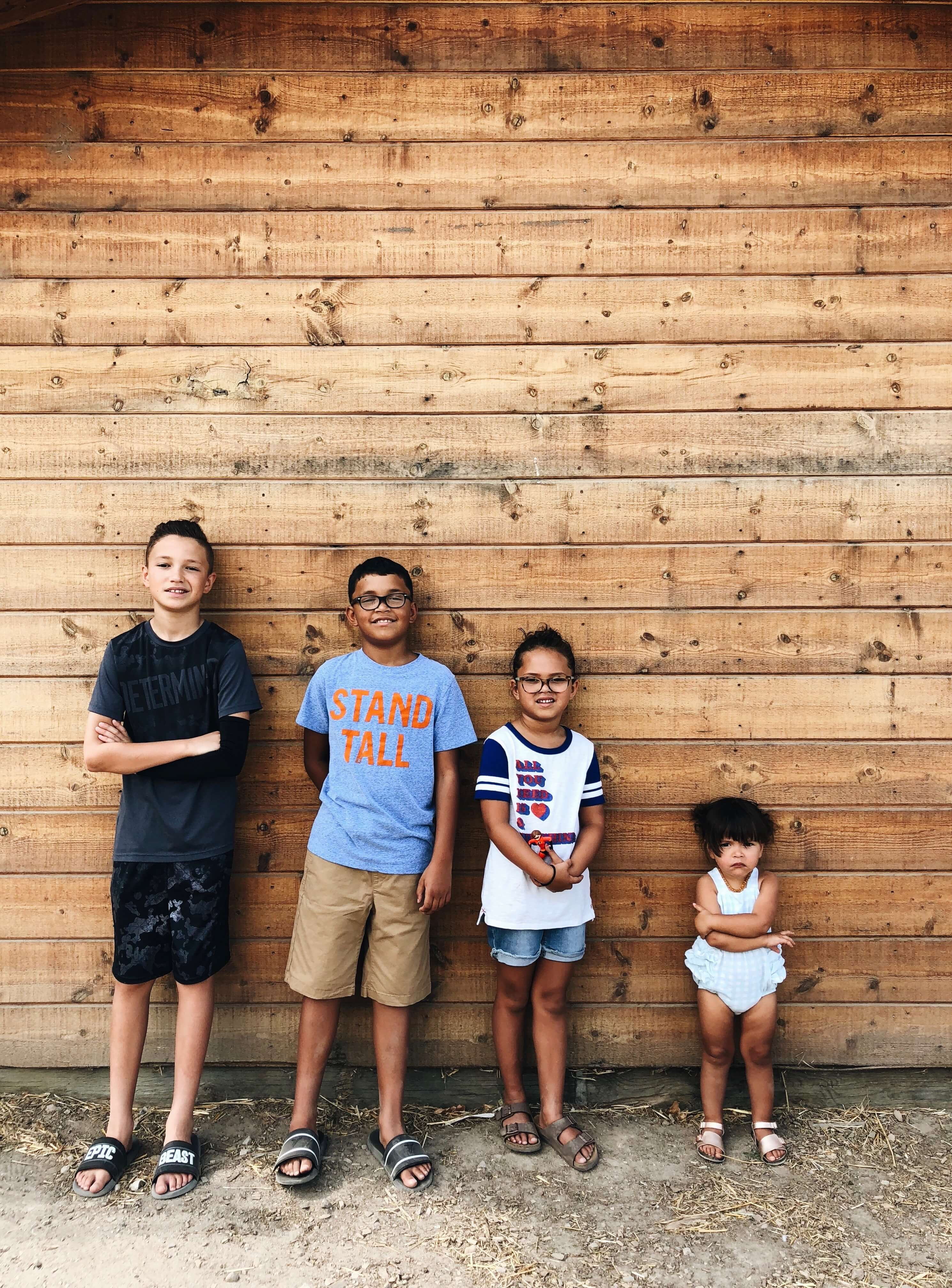 Four kids standing against wall in order of height