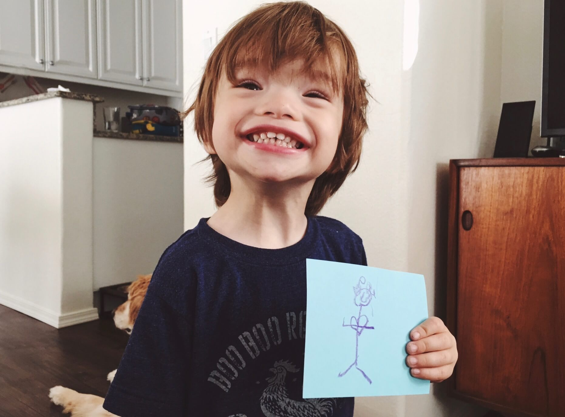 Little boy holding up artwork and smiling proudly