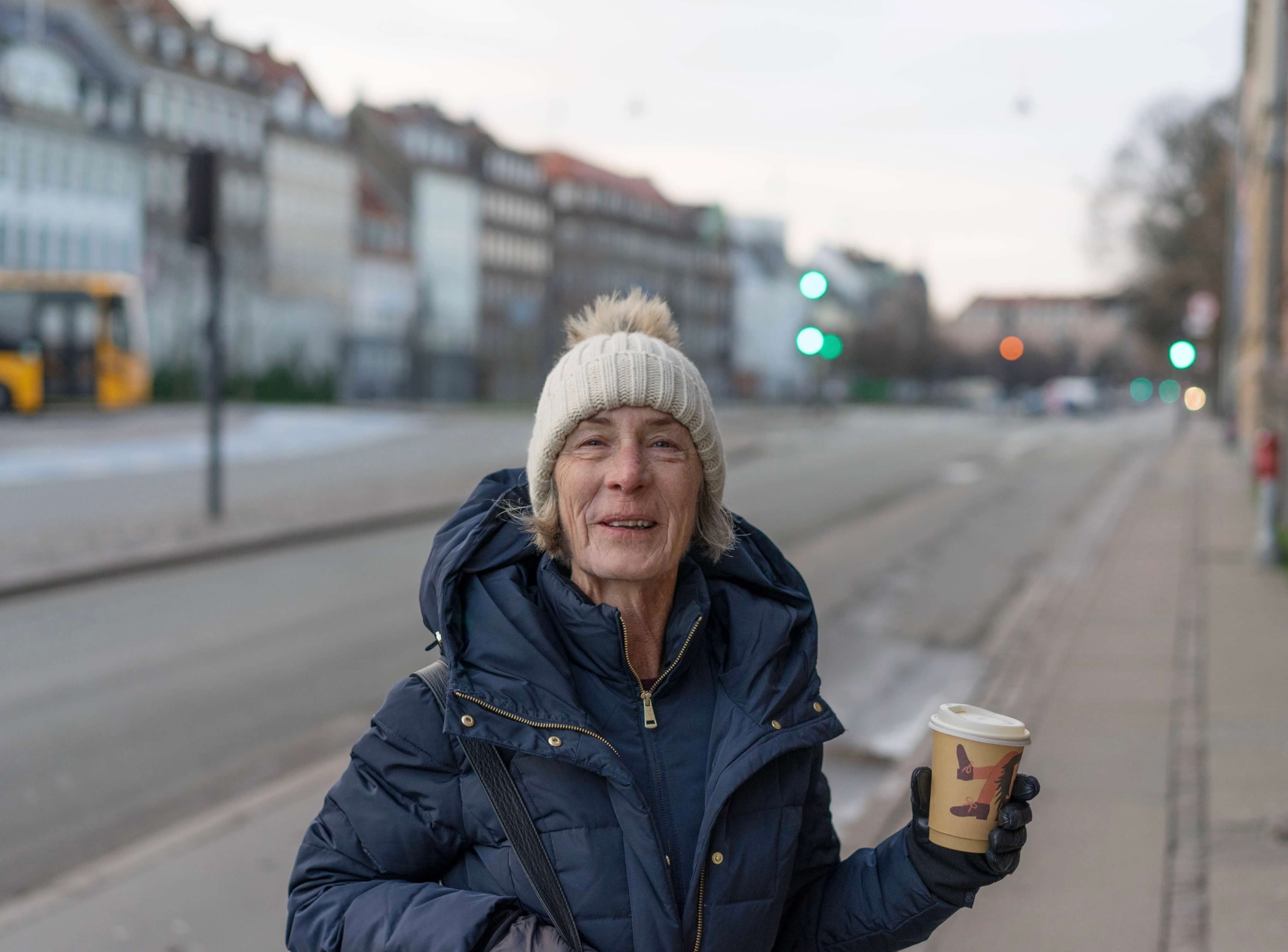 Woman bundled up in large jacket holding coffee cup with surprised smile on her face