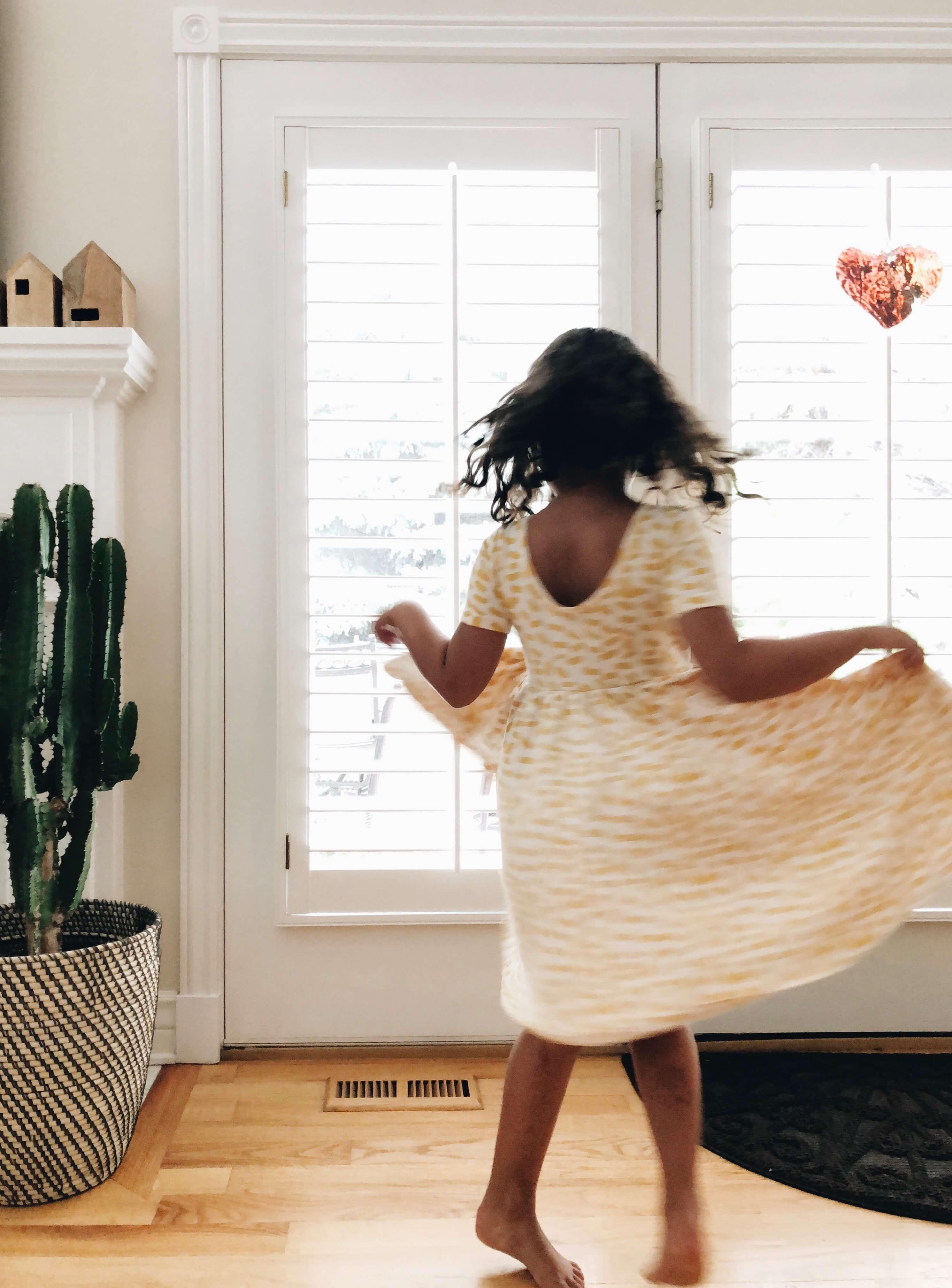 Blurry photo of little girl in polka-dot dress twirling whimsically