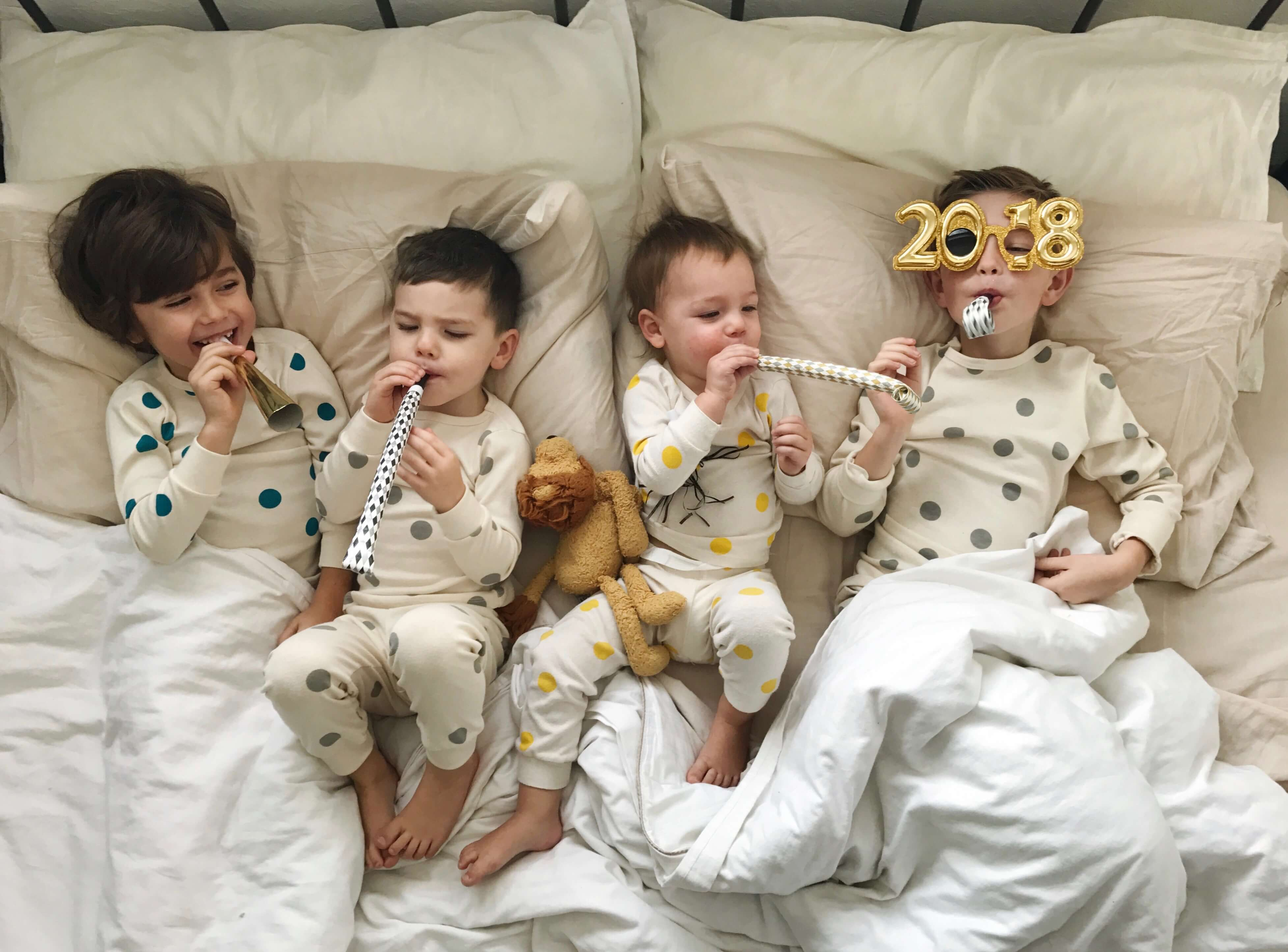 Four children lying in bed with new year's props