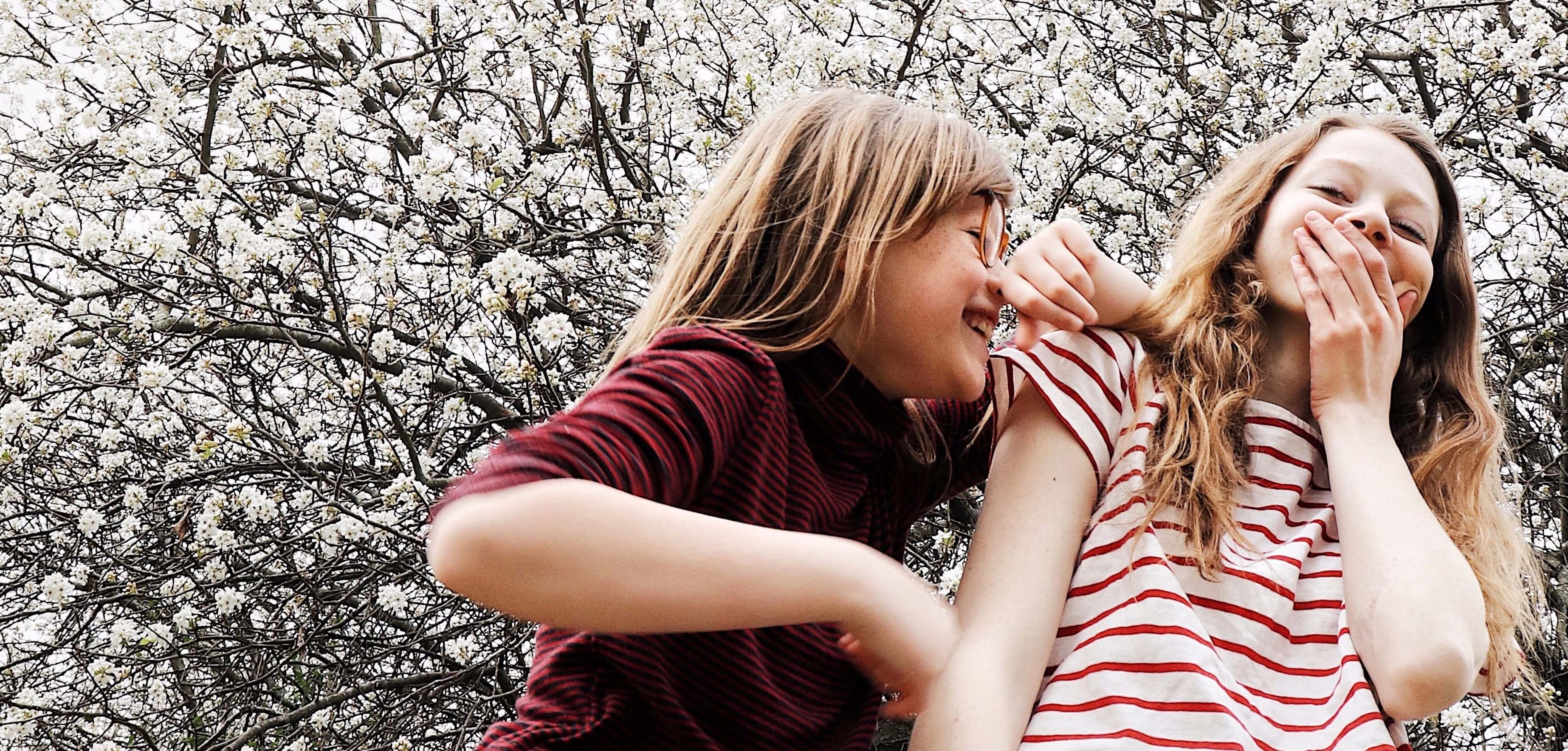 Two little girls laughing with flowering tree in the background
