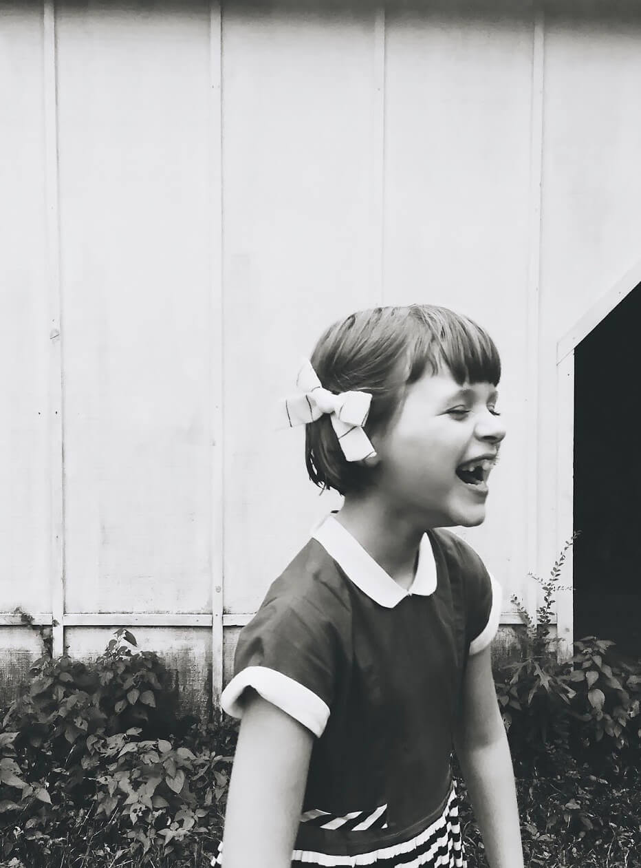 Black and white photo of little girl with bow in her hair laughing