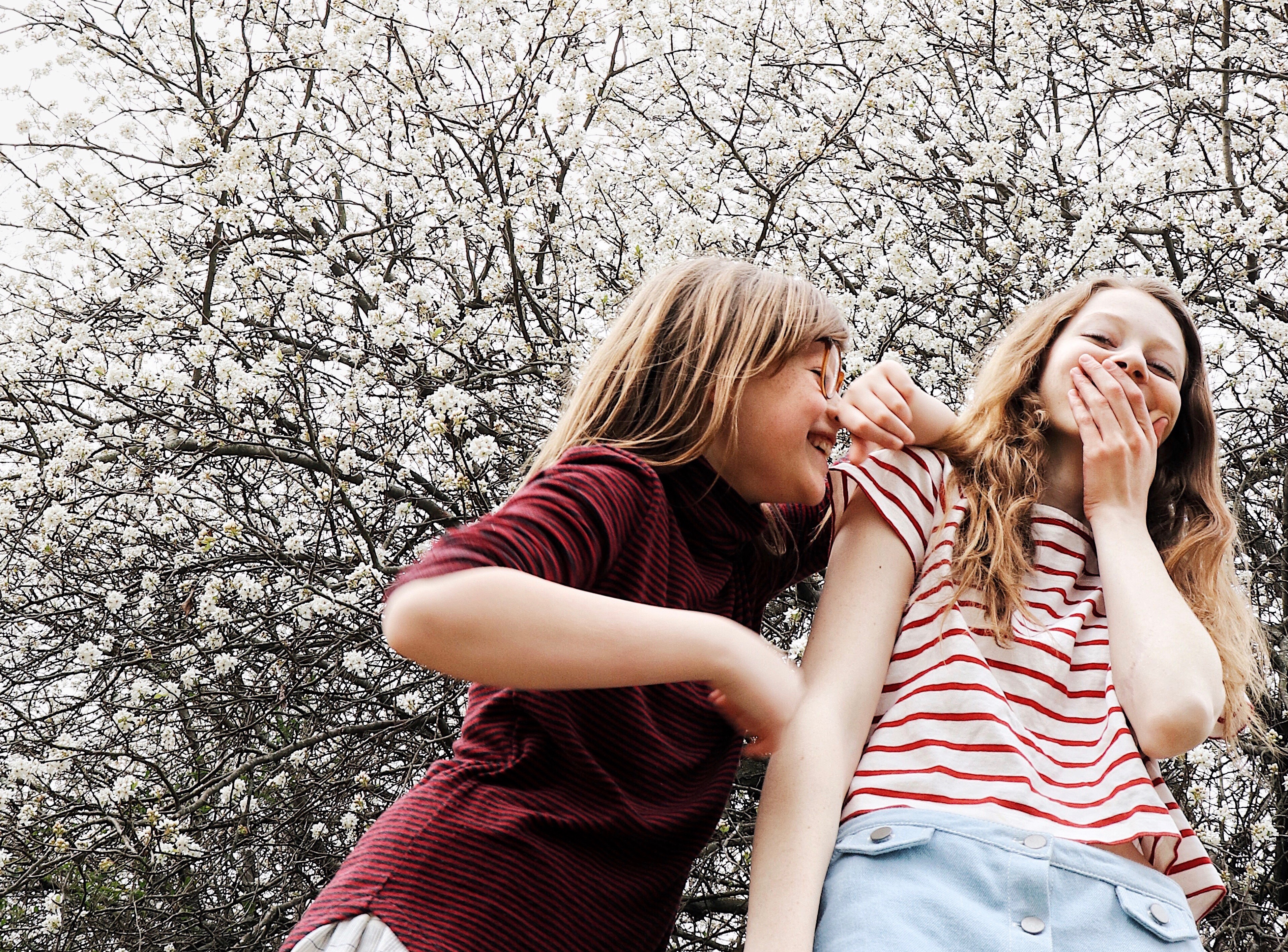 Two sisters laughing in front of flowering tree