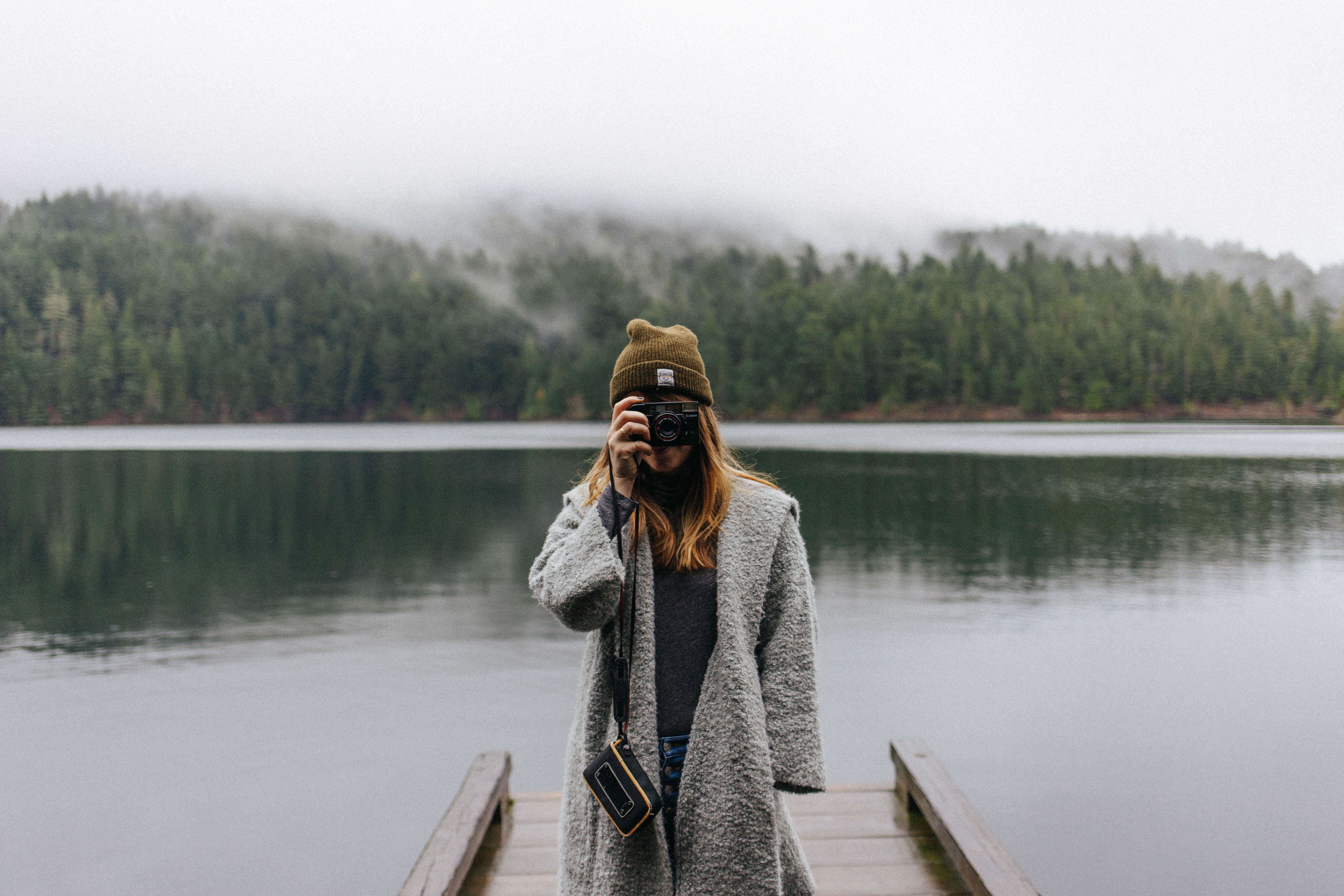 Photo of woman taking a picture with camera pointed at screen