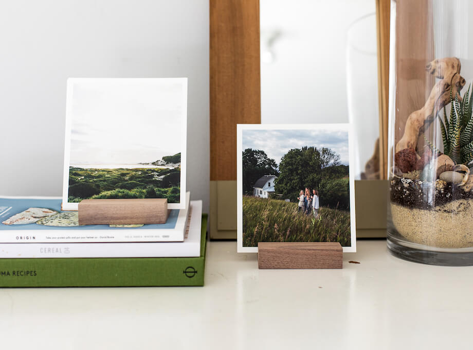 Photo prints on desk held by wooden photo holders