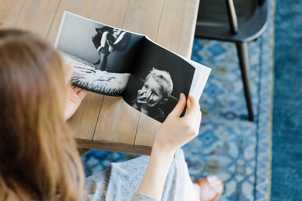 Woman flipping through softcover photo book at dining table