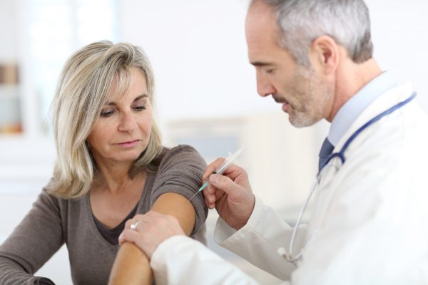 Doctor injecting vaccine to senior woman