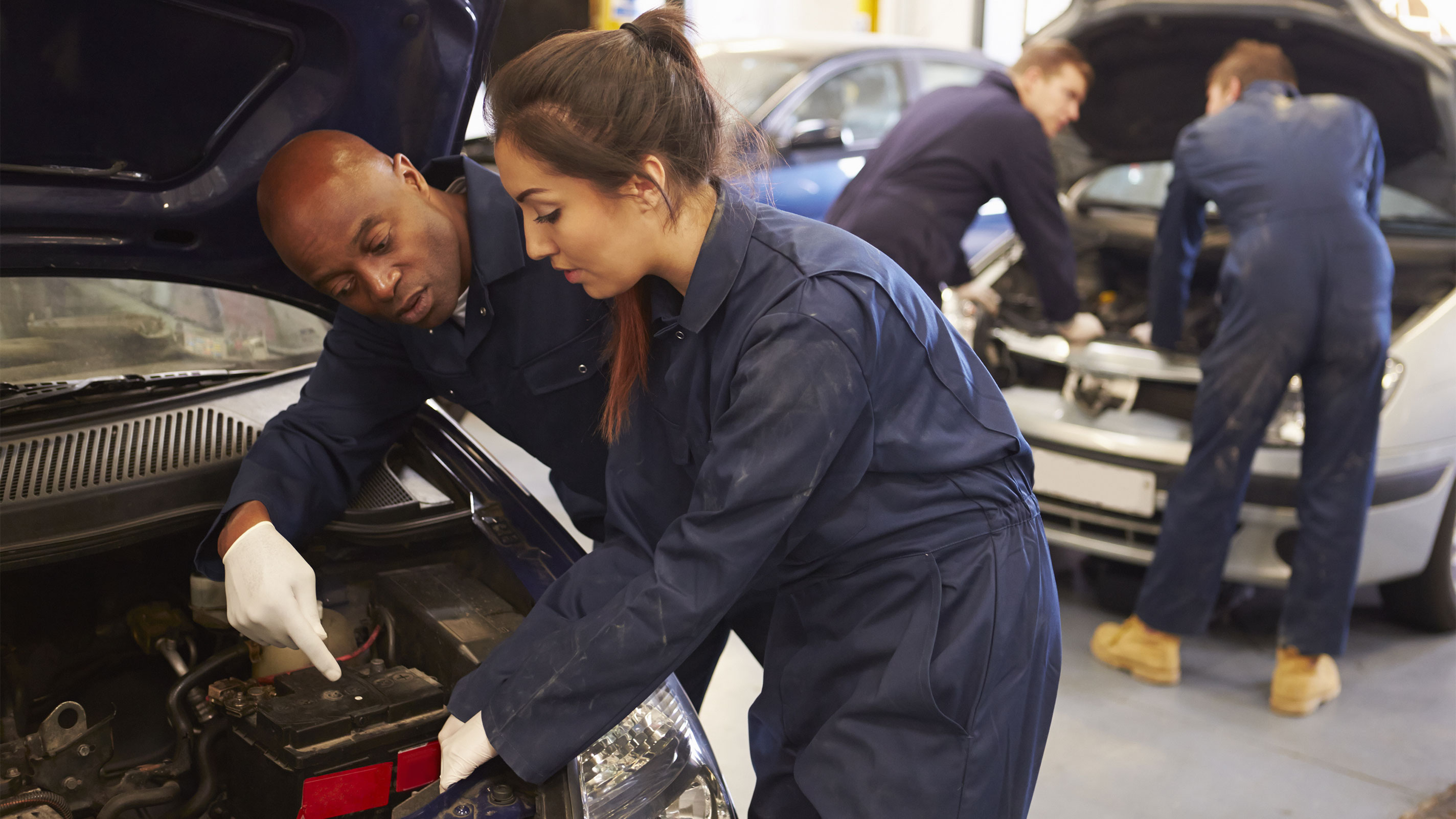 Young woman works on a car engine with her instructor
