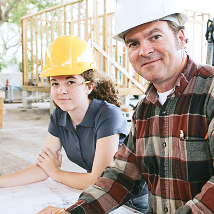 Young woman and older man wearing hard hats and looking at blueprints