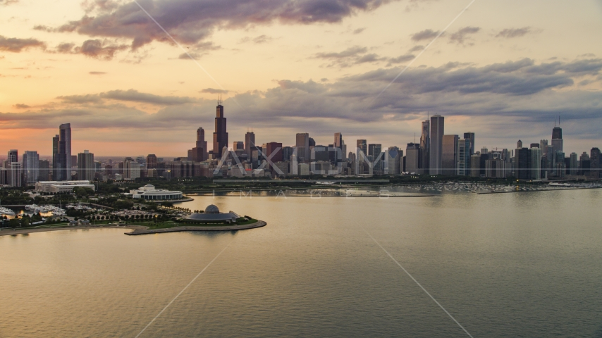 A view of Downtown Chicago skyline and the Adler Planetarium seen from Lake Michigan, at sunset, Illinois Aerial Stock Photo AX0003_029.0000188F | Axiom Images