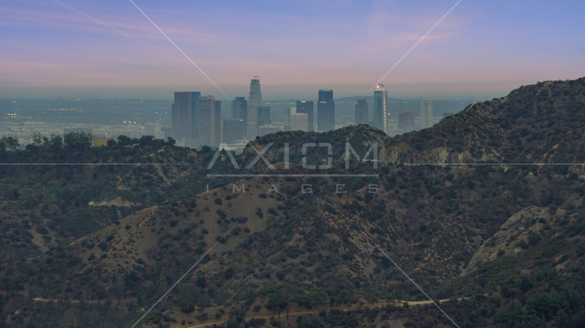 Downtown Los Angeles seen from behind a hill, twilight, California Aerial Stock Photos | AX0158_004.0000052