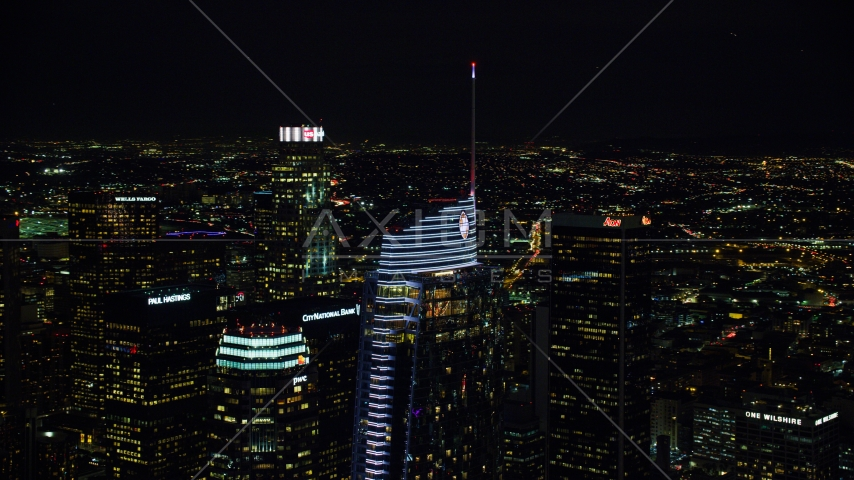 The top of Wilshire Grand Center at night in Downtown Los Angeles, California Aerial Stock Photos | AX0158_113.0000337