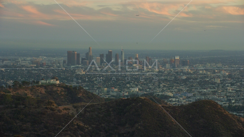 The skyline of Downtown Los Angeles, California at twilight and Griffith Observatory Aerial Stock Photos | AX0162_105.0000154