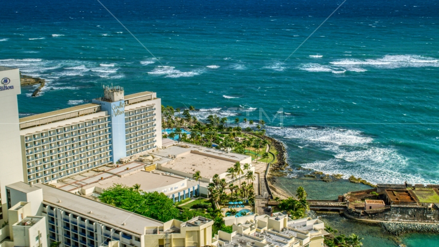 Caribe Hilton Hotel oceanside resort in the Caribbean, San Juan, Puerto Rico Aerial Stock Photo AX101_004.0000122F | Axiom Images