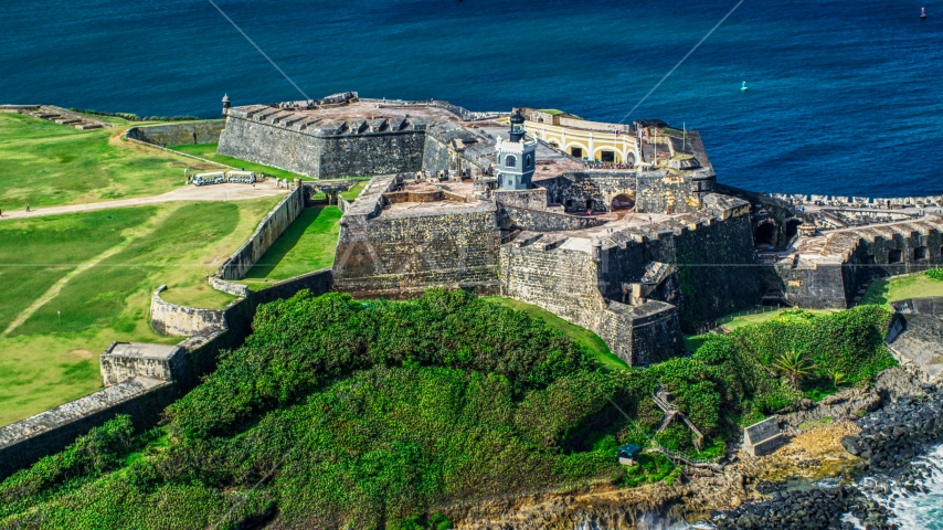 A historic fort and lighthouse beside blue waters, Old San Juan, Puerto Rico Aerial Stock Photo AX101_026.0000000F | Axiom Images