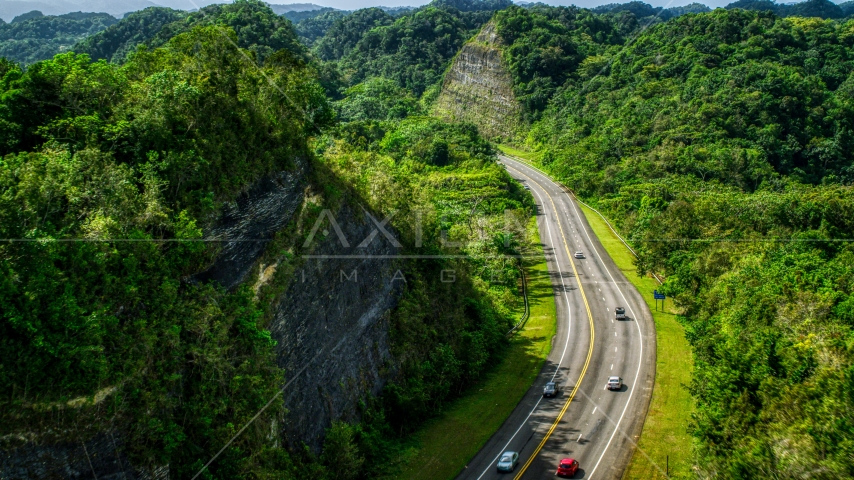 Light highway  traffic through lush green mountains, Karst Forest, Puerto Rico  Aerial Stock Photos | AX101_078.0000299F