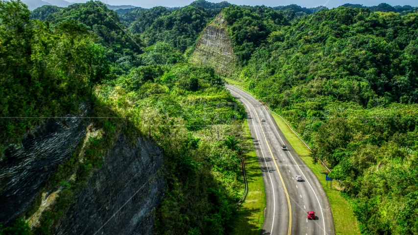 Highway with light traffic through lush green mountains, Karst Forest, Puerto Rico Aerial Stock Photo AX101_079.0000000F | Axiom Images