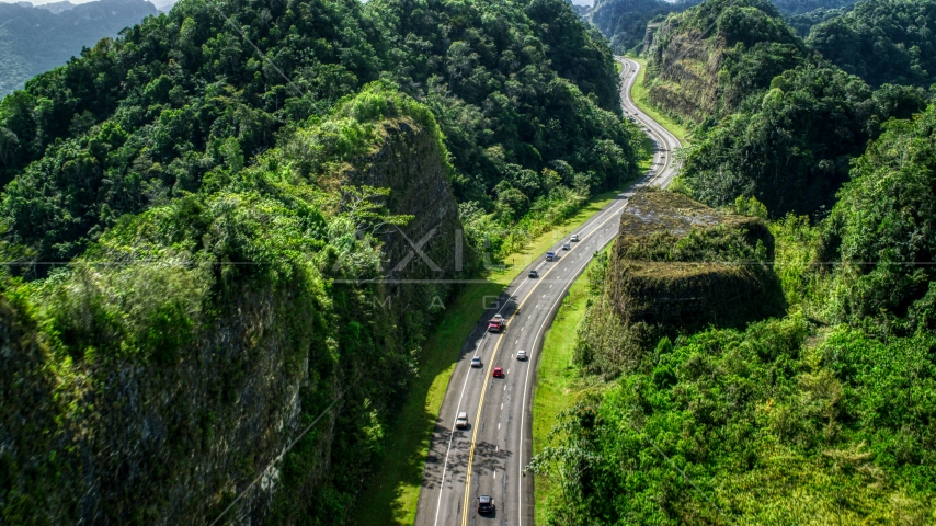 Light traffic on a highway lush green mountains, Karst Forest, Puerto Rico Aerial Stock Photos | AX101_082.0000065F