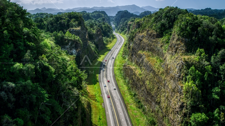 A highway through lush green mountains, Karst Forest, Puerto Rico Aerial Stock Photo AX101_083.0000200F | Axiom Images