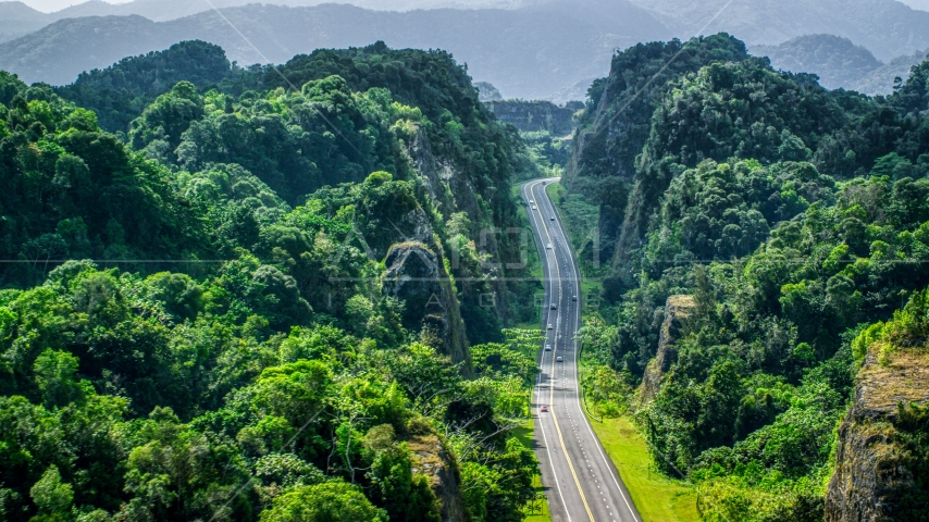 A highway cutting through lush green mountains, Karst Forest, Puerto Rico Aerial Stock Photos | AX101_085.0000000F