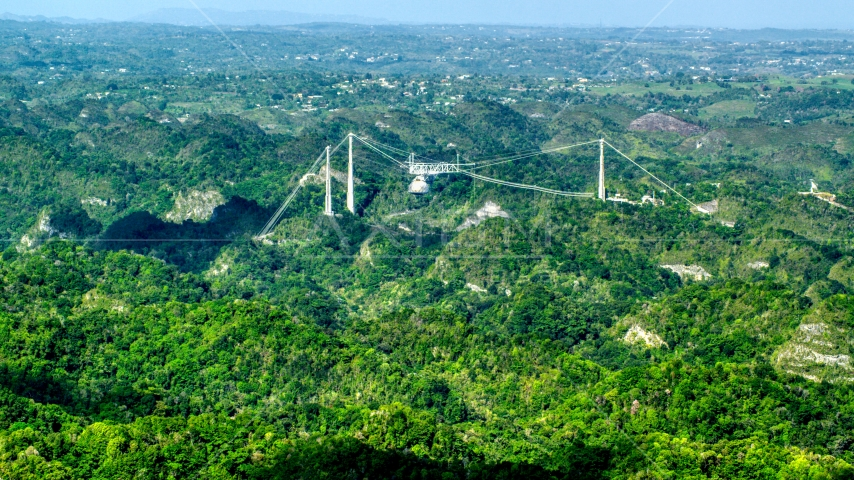 Arecibo Observatory rising above the lush green Karst Forest, Puerto Rico  Aerial Stock Photos | AX101_087.0000000F