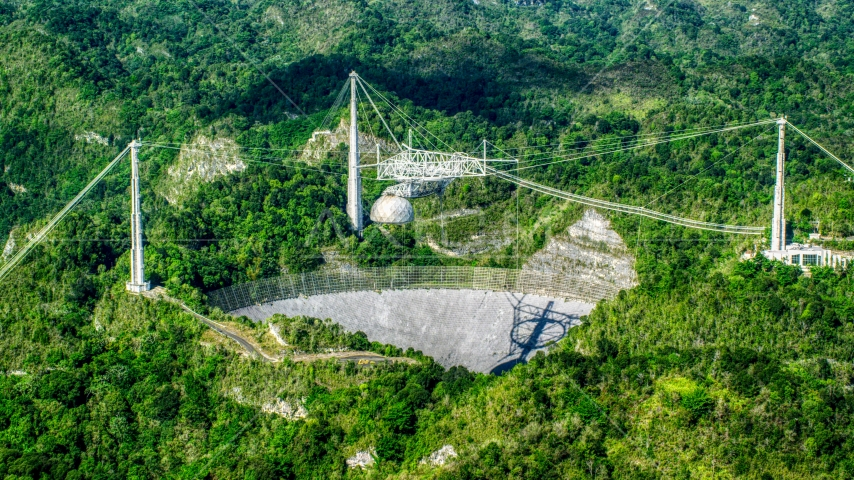 Wide shot of the Arecibo Observatory among lush green forests, Puerto Rico  Aerial Stock Photos | AX101_090.0000276F