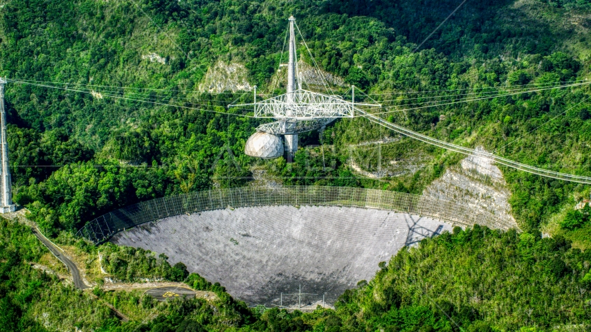 A view of the Arecibo Observatory in the lush green Karst forest, Puerto Rico Aerial Stock Photo AX101_091.0000000F | Axiom Images