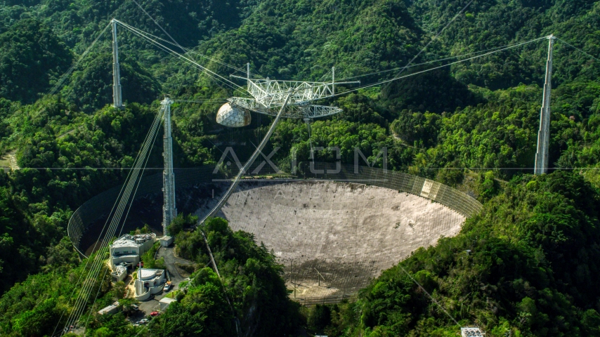 A view of the Arecibo Observatory surrounded by trees, Puerto Rico Aerial Stock Photo AX101_105.0000000F | Axiom Images