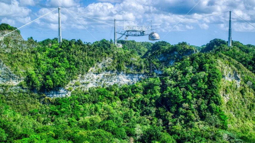 Top of the Arecibo Observatory seen above karst mountains, Puerto Rico Aerial Stock Photo AX101_114.0000000F | Axiom Images