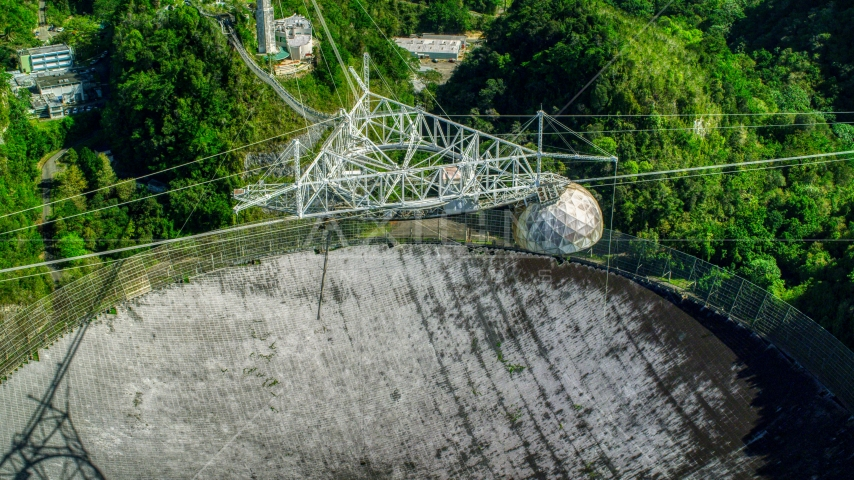 Looking downward at the Arecibo Observatory surrounded by trees, Puerto Rico Aerial Stock Photo AX101_117.0000306F | Axiom Images