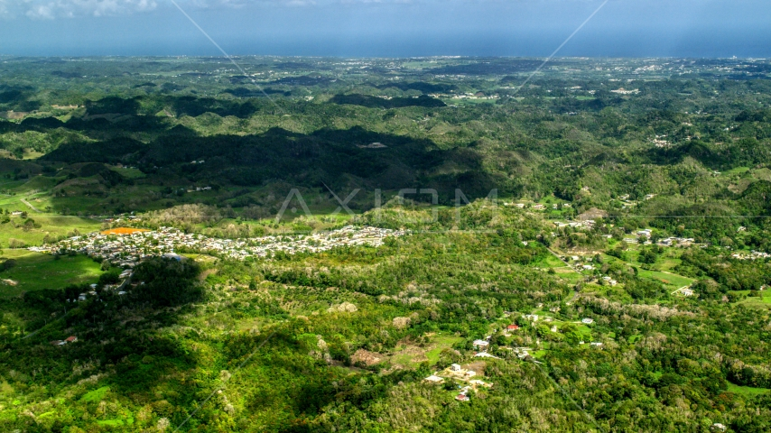 Rural homes and tree covered karst mountains, Arecibo, Puerto Rico Day Partly Cloudy Side View Aerial Stock Photo AX101_125.0000000F | Axiom Images