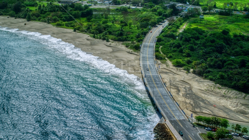Coastal road cutting through trees and over a beach by blue water, Arecibo, Puerto Rico  Aerial Stock Photos | AX101_140.0000000F