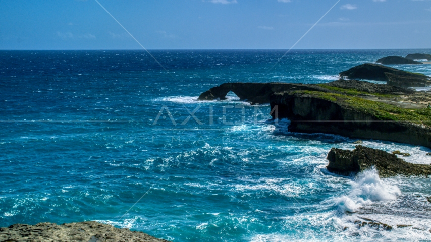 A rock arch in the blue water of a Caribbean island, Arecibo, Puerto Rico  Aerial Stock Photo AX101_161.0000329F | Axiom Images