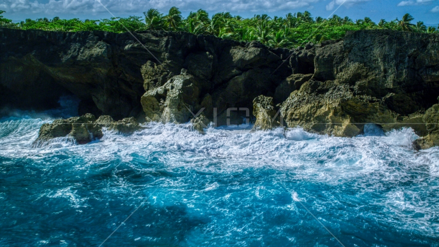 Coastal rock formations and caves, and crashing ocean waves in Arecibo, Puerto Rico  Aerial Stock Photo AX101_163.0000000F | Axiom Images