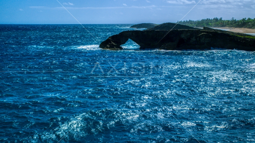 An arched rock formation in crystal blue water, Arecibo, Puerto Rico Aerial Stock Photos | AX101_168.0000129F