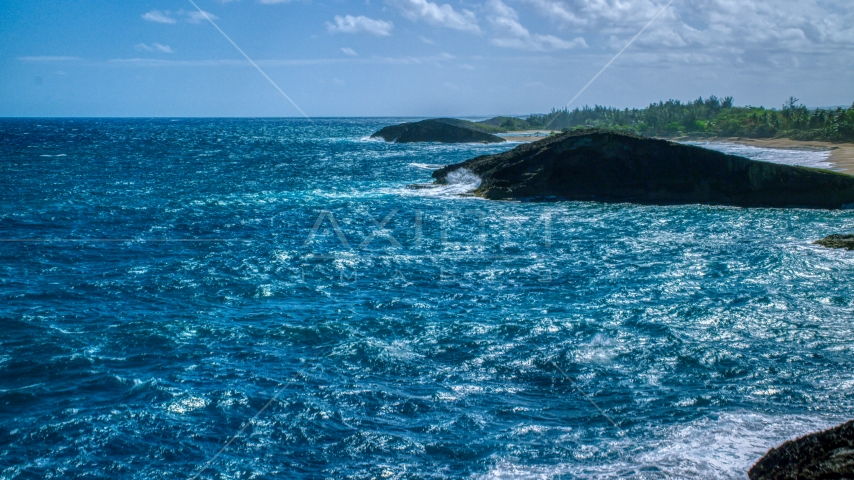 Domed rock formation in crystal blue waters, Arecibo, Puerto Rico Aerial Stock Photo AX101_169.0000312F | Axiom Images