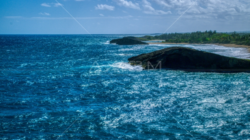A pair of domed rock formations in crystal blue waters on the coast, Arecibo, Puerto Rico  Aerial Stock Photo AX101_170.0000000F | Axiom Images