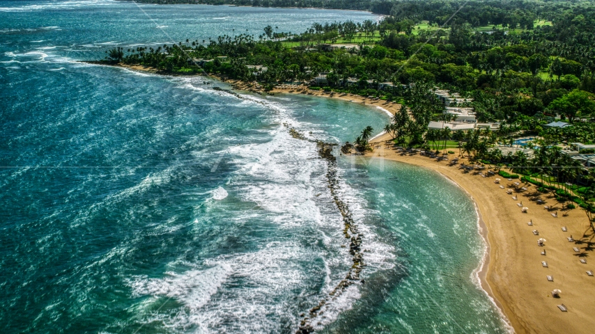 Waves hitting the breakwater by a Caribbean beach resort in Dorado, Puerto Rico  Aerial Stock Photos | AX101_214.0000000F